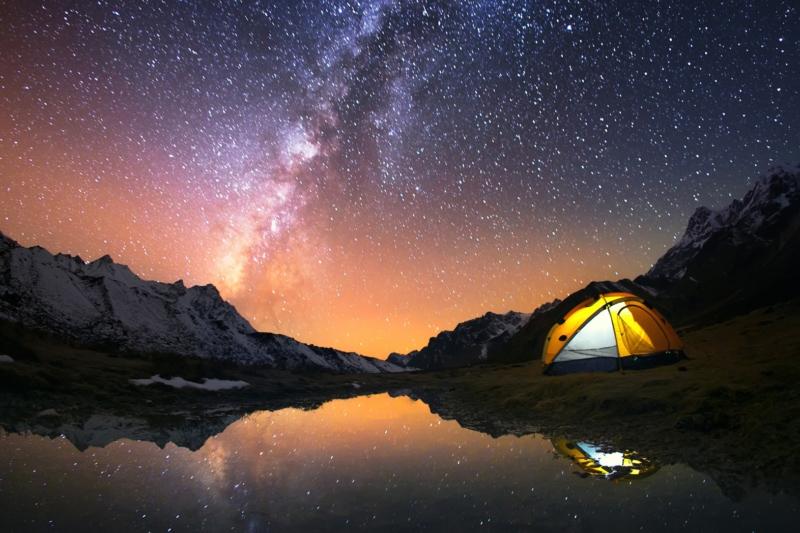 Взгляд звезд и палатки рюкзаки ночью на озере