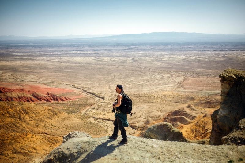 фотограф с рюкзаком, стоя на выступе с видом на пустыню
