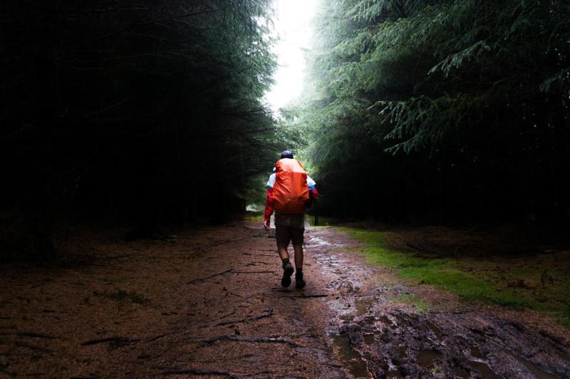 Человек с оранжевым рюкзаком, прогуливаясь по грязной тропе